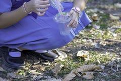 Fille asiatique de main tenant un verre de pailles à boire en plastique et de rebut colorées photos stock