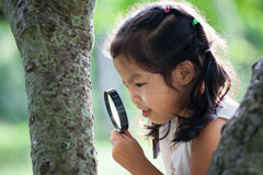 Fille asiatique de petit enfant regardant par une loupe Image stock