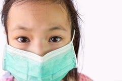 Fille asiatique de portrait petite dans un masque médical d'isolement sur le fond blanc, enfant portant le masque hygiénique, con photo libre de droits