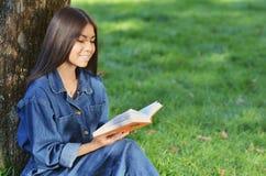 Fille asiatique de sourire d'étudiant s'asseyant et travaillant au livre se préparant aux examens dehors, ayant le repos dans le  photos libres de droits