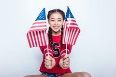 Fille asiatique de sourire dans le pull molletonné rouge reposant et tenant de petits drapeaux américains Photo stock