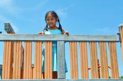 Fille asiatique de sourire de jeunes se tenant sur l'équipement de terrain de jeu de gymnase Image libre de droits