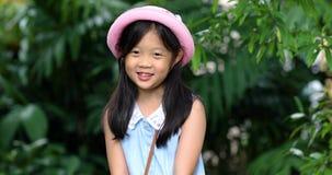 Fille asiatique de sourire L'enfant est prêt pour le déplacement Enfant riant avec bonheur banque de vidéos