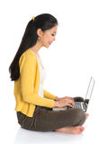 Fille asiatique de vue de côté à l'aide de l'ordinateur portable photo stock