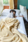 Fille asiatique dormant sur le lit couvert de couverture Photos libres de droits