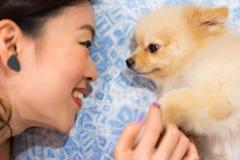 Fille asiatique et son chien mignon regardant fixement dans les yeux de chacun Photographie stock