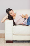 Fille asiatique gaie se trouvant sur le divan lisant un magazine Images libres de droits
