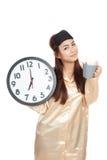 Fille asiatique heureuse avec le masque d'oeil, la tasse de café et l'horloge photos libres de droits