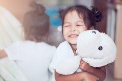 Fille asiatique heureuse d'enfant souriant et étreignant sa poupée avec amour Photographie stock