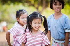 Fille asiatique heureuse d'enfant souriant et jouant avec son ami Images stock