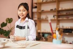 Fille asiatique heureuse dans la classe de poterie image stock