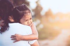 Fille asiatique heureuse de petit enfant étreignant sa mère avec amour Image libre de droits