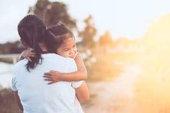 Fille asiatique heureuse de petit enfant étreignant sa mère avec amour Images libres de droits
