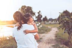 Fille asiatique heureuse de petit enfant étreignant sa mère avec amour Photo libre de droits