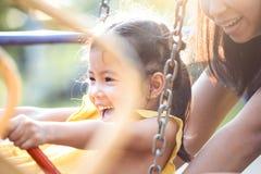 Fille asiatique heureuse de petit enfant ayant l'amusement à monter sur des oscillations Photo stock