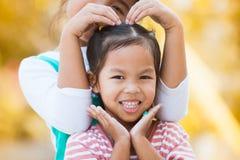 Fille asiatique heureuse de petit enfant faisant la main dans la forme de coeur Photo stock