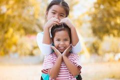 Fille asiatique heureuse de petit enfant faisant la main dans la forme de coeur Images stock