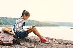 Fille asiatique heureuse lisant un livre en nature Image libre de droits