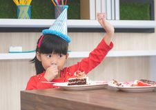 Fille asiatique heureuse mangeant son gâteau d'anniversaire, demandant plus de Ca photographie stock libre de droits