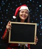 Fille asiatique heureuse portant Santa Costume Christmas Holding Blackbo image stock
