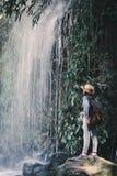 Fille asiatique heureuse se tenant sur le fond de pierre et de cascade Photos stock