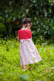Fille asiatique jouant avec des bulles de savon sur le fond de nature surpassez Images stock