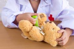 Fille asiatique jouant comme poupée d'ours de soin de docteur images libres de droits