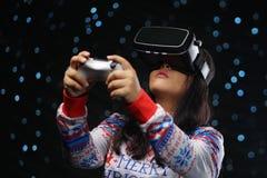 Fille asiatique jouant des jeux vidéo avec du Sn foncé de lueur de réalité virtuelle images stock