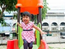 Fille asiatique jouant le glisseur après le sable de jeu sur le terrain de jeu Images libres de droits