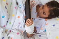 Fille asiatique malade de petit enfant à l'aide du comprimé numérique image stock