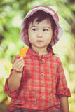 Fille asiatique mangeant la crème glacée pendant l'été sur le dos brouillé de nature Image stock