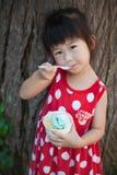 Fille asiatique mangeant la crème glacée pendant le jour d'été outdoors Photo stock