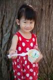 Fille asiatique mangeant la crème glacée pendant le jour d'été outdoors Photographie stock libre de droits