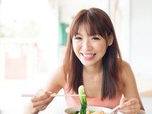 Fille asiatique mangeant les nouilles végétales Photographie stock libre de droits