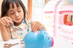 Fille asiatique mettant la pièce de monnaie à la tirelire pour l'argent économisant Centre sélectif de main d'enfant photo stock