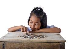 Fille asiatique mignonne comptant et pièces de monnaie de pile pour économiser d'isolement sur le fond blanc photos stock