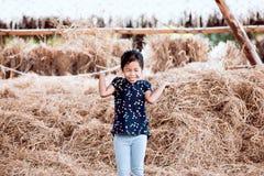 Fille asiatique mignonne d'enfant ayant l'amusement à jouer avec la pile de foin Photos stock