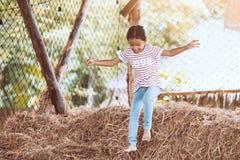 Fille asiatique mignonne d'enfant ayant l'amusement à sauter et jouer avec la pile de foin Photos libres de droits