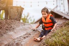 Fille asiatique mignonne d'enfant ayant l'amusement pour jouer le glisseur boueux Photographie stock libre de droits