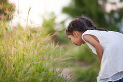 Fille asiatique mignonne d'enfant jouant avec la nature Photo libre de droits