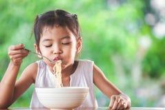 Fille asiatique mignonne d'enfant mangeant les nouilles instantanées délicieuses avec la fourchette photo stock