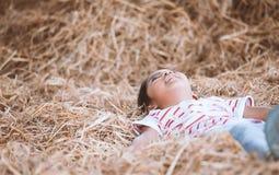 Fille asiatique mignonne d'enfant se couchant sur le foin et le jeu avec la pile de foin Image stock