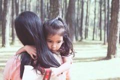 Fille asiatique mignonne de petit enfant étreignant sa mère avec amour Photographie stock