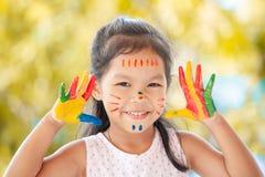 Fille asiatique mignonne de petit enfant avec les mains peintes souriant avec l'amusement Photos stock