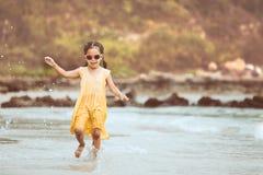 Fille asiatique mignonne de petit enfant ayant l'amusement à jouer et la course sur la plage Photo libre de droits
