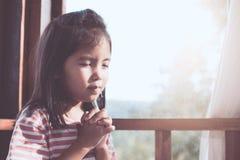 Fille asiatique mignonne de petit enfant priant avec plié sa main images libres de droits