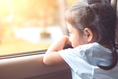 Fille asiatique mignonne de petit enfant s'asseyant dans la voiture Photo stock