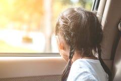 Fille asiatique mignonne de petit enfant s'asseyant dans la voiture Images stock