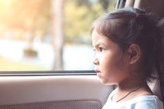 Fille asiatique mignonne de petit enfant s'asseyant dans la voiture Image libre de droits