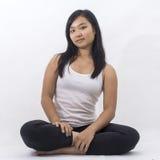Fille asiatique mignonne sur le fond d'isolement méditant image libre de droits